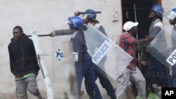 Armed Zimbabwean police clash with rioters in Harare, Monday, July 4, 2016. (AP Photo/Tsvangirayi Mukwazhi)