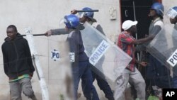 FILE: Armed Zimbabwean police clash with rioters in Harare, Monday, July 4, 2016. (AP Photo/Tsvangirayi Mukwazhi)