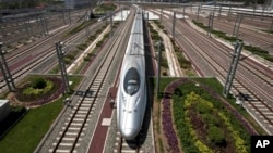 FILE - In this July 26, 2011 file photo, a CRH high-speed train leaves the Beijing South Station in Beijing.