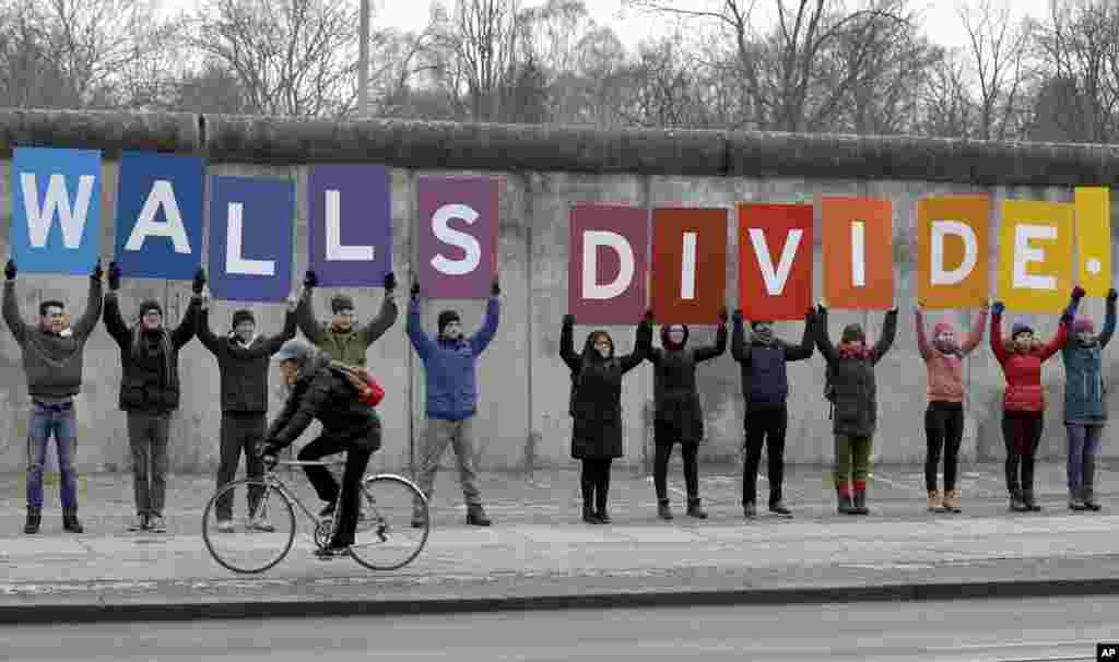 Les manifestants de l'organisation environnementale 'Greenpeace' affichent des pancartes montrant une partie d'un slogan au Mémorial du Mur de Berlin à Berlin, en Allemagne, le vendredi 20 janvier 2017. Le slogan complet se lit comme suit: «M. Président, les murs se divisent, construisent des ponts! '. Le président élu américain Donald Trump sera inauguré plus tard dans la journée.