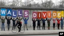 Des manifestants de l'organisation environnementale 'Greenpeace' avec des pancartes disant 'Les murs divisent', près du Mémorial du Mur de Berlin, en Allemagne, 20 janvier 2017