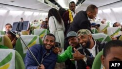 Passengers pose for a selfie picture inside an Ethiopian Airlines flight which departed from the Bole International Airport in Addis Ababa, Ethiopia, to Eritrea's capital Asmara on July 18, 2018.