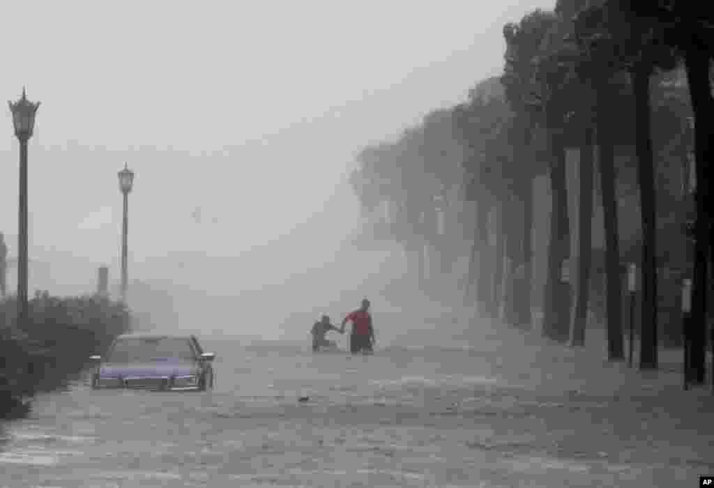 허리케인 '이마'가 강타한 미국 사우스캐롤라이나주 찰스턴에서 주민들이 물에 잠긴 도로를 건너고 있다.