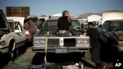 Three men salvage parts gather from a junk car at Aadlen Brothers Auto Wrecking, also known as U Pick Parts, Sun Valley section of Los Angeles, Nov. 11, 2015.