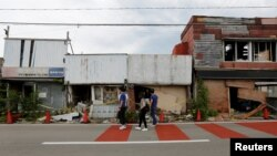 Tourists from Philippines walk past damaged retail stores near Tokyo Electric Power Co's tsunami-crippled Fukushima Daiichi nuclear power plant, in Namie town, Fukushima prefecture, Japan, May 17, 2018.