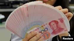 Seorang karyawan di sebuah bank di Taipei menghitung lembaran uang kertas China, Yuan, 6 Februari 2013.