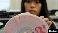 An employee counts Chinese yuan notes inside a bank in Taipei, Feb. 6, 2013.