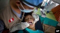 Un dentista revisa los dientes a un muchacho peruano en Surcubamba.
