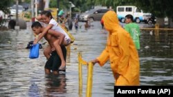 A Filipino man carries a girl as they negotiate a flooded street after a heavy downpour in suburban Quezon city, north of Manila, Philippines on Wednesday, June 17, 2015. AP Photo/Aaron Favila)