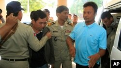 Chay Sarith (2-L) and Mao Hoeun (2-R) in light blue shirt, suspected attackers accused of beating two opposition lawmakers, are escorted by police officers at Phnom Penh Municipal Court in Phnom Penh, Cambodia, Nov. 4, 2015.