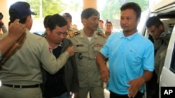 Chay Sarith, second left, and Mao Hoeun, second right in light blue shirt, suspected attackers who are accused of beating two opposition lawmakers along with another man, are escorted by police officers at Phnom Penh Municipal Court in Phnom Penh, Cambodia, Wednesday, Nov. 4, 2015. Three suspects of the assault outside of the National Assembly last week made confessions on Tuesday, according to a government statement released late Tuesday. (AP Photo/Heng Sinith)