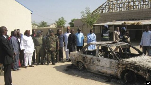 Bystanders gather around a burned car outside the Victory Baptist Church in Maiduguri, Nigeria. Police are blaming members of Boko Haram for the attack on church (File photo - December 25, 2010)