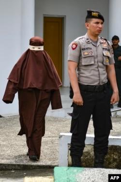 Perempuan pertama yang menjadi eksekutor hukuman cambuk tiba di lokasi pelaksanaan hukuman cambuk untuk seorang terpidana perempuan di Banda Aceh, 10 Desember 2019. (Foto: AFP)