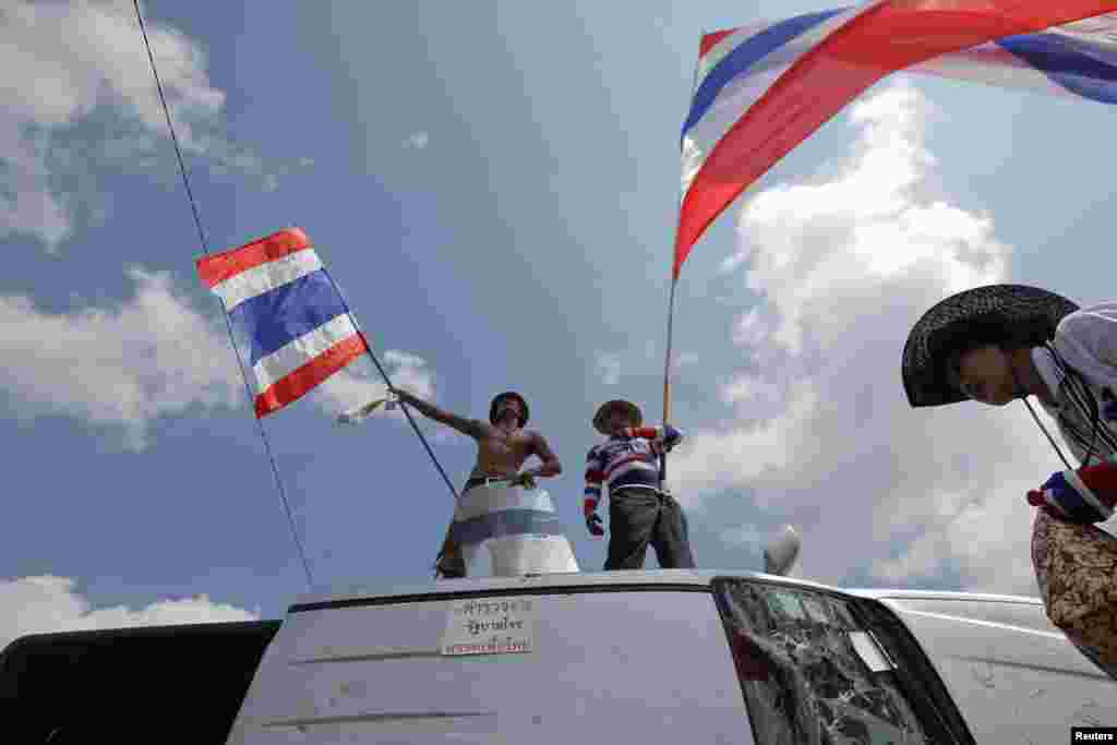 Anti-government protesters celebrate on top of a destroyed police vehicle after clashes near the Government House in Bangkok, Feb. 18, 2014.