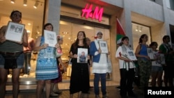 Demonstrators stand outside a store of Swedish fashion firm H&M during a protest against the Israeli offensive in Gaza, in Valencia, Spain, Aug. 7, 2014.