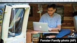 FILE - In this 2018 photo, Danny Fenster works out of his van that he made into a home/office in Detroit, Michigan.