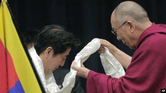Pemimpin Spiritual Tibet, Dalai Lama (kanan) mengalungkan selendang putih khas Tibet untuk pemimpin partai Demokratik Liberal Jepang, Shinzo Abe di Tokyo (13/11).