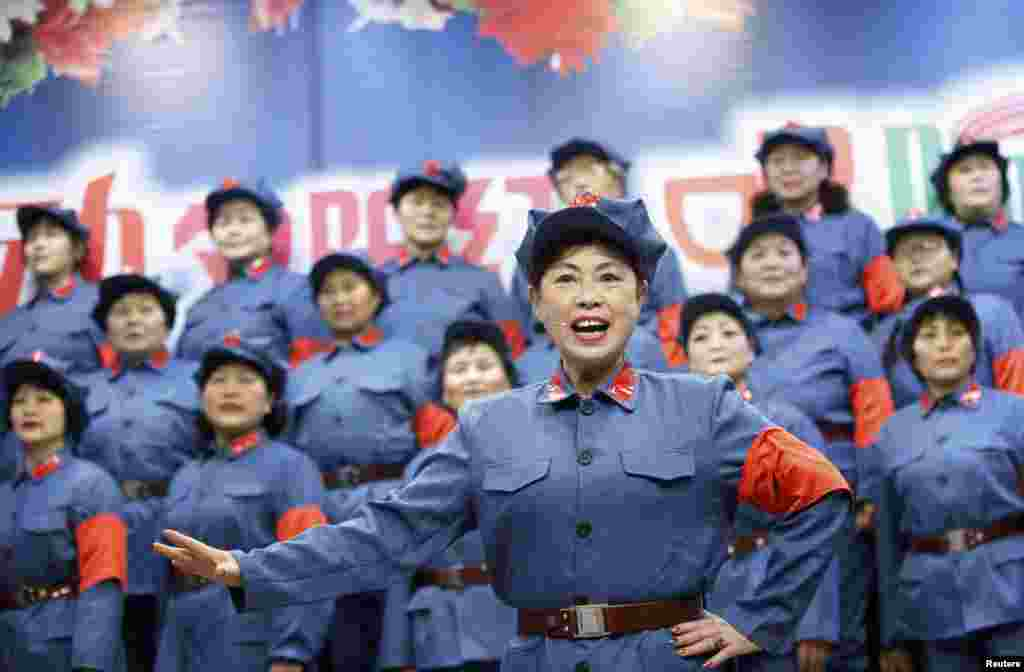 Retired female workers dressed as red army soldiers sing revolutionary songs during a performance to mark the 120th birth anniversary of Mao Zedong in Huaibei, Anhui province, China, Dec. 26, 2013.