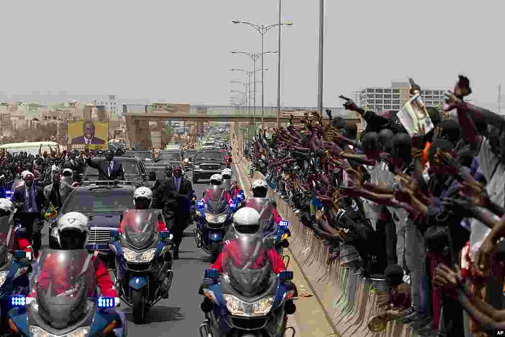 Senegal's newly inaugurated President Macky Sall waves to supporters from his convoy as he travels to the presidential palace to take up residence, in Dakar. (AP)