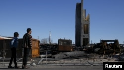 FILE - People stand outside the burned community center and apartments across the street from the Southern Baptist Church in Baltimore, Maryland, April 28, 2015.