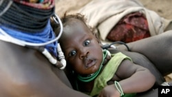 A Turkana woman carries her child at a peace meeting in the Lobei Kraal village of Turkana district in North-western Kenya (file photo)
