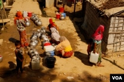 Women line up to fill containers with drinking water at the Rohingya refugee camp in Teknaf, Bangladesh on Feb. 12, 2020. (Hai Do/VOA)
