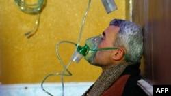 Seorang pria Suriah mengenakan masker oksigen di sebuah rumah sakit darurat, menyusul laporan serangan gas di Douma, kota yang dikuasai pemberontak di timur wilayah Ghouta, di pinggiran Ibu Kota Damascus, 22 Januari 2018. (Foto:Dok)