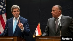U.S. Secretary of State John Kerry, left, speaks during a joint news conference with Egyptian Foreign Minister Sameh Shoukry following his meeting with Egyptian President Abdel-Fattah el-Sissi in Cairo, Egypt, June 22, 2014.