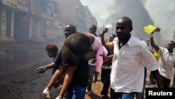 April 29: People carry an injured protester, shot by Ugandan military forces, in Kampala. Ugandan police fired live bullets and tear gas on Friday to disperse crowds.
