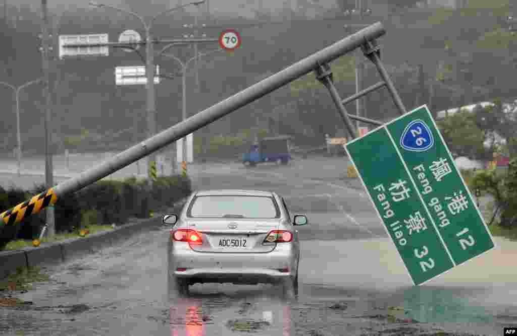 A car drives pass a collapsed traffic sign, toppled by strong winds of typhoon Meranti, as it slashes southern Taiwan.