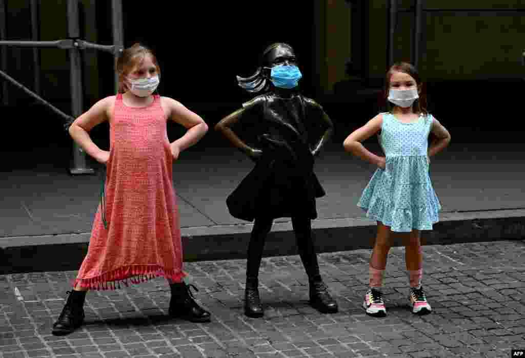 """Девојчиња со заштитни маски позираат со скулптурата """"Бестрашно девојче"""" (Photo by Johannes EISELE / AFP)"""