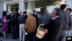 Gradjani čekaju u redu ispred banke na Kipru