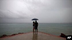 FILE - A couple looks out to sea as hurricane-related rainfall increases in Puerto Vallarta, Mexico.