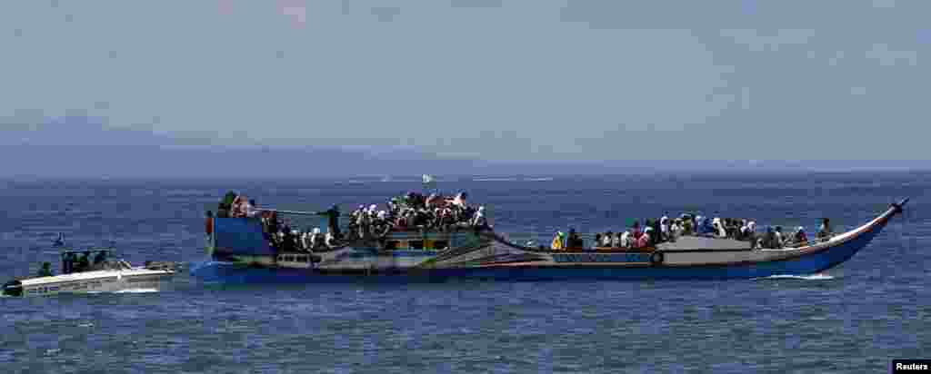A police patrol boat escorts villagers after they were evacuated from their homes due to fighting between government soldiers and Muslim rebels, near Zamboanga, Philippines, Sept. 17, 2013.