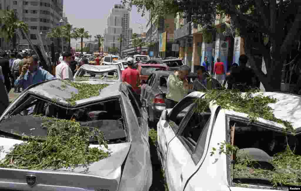 People walk on a street lined with a damaged building and destroyed cars after a blast at Marjeh Square in Damascus, April 30, 2013.