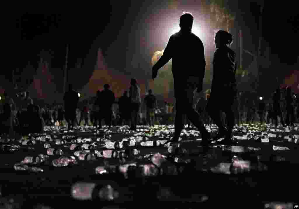 April 18: Music fans walk through water bottles towards the exit at the end of the Coachella Music & Arts Festival, early Monday morning in Indio, Calif. (AP Photo/Spencer Weiner)