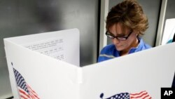 FILE - Ellen Sathe votes at Santa Clara County Registrar of Voters, Oct. 24, 2016, in San Jose, California, where voting rights advocates say they will monitor more polling places than usual on Election Day amid concerns about possible voter intimidation stemming from GOP presidential nominee Donald Trump's repeated assertions that the election is rigged against him.