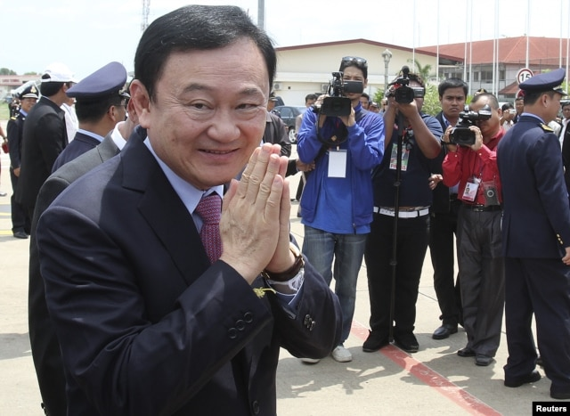 FILE - Former Thai prime minister Thaksin Shinawatra greets the media upon his arrival at the Siem Reap International Airport in Cambodia, April 14, 2012.