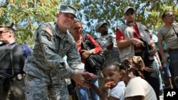 US Army special forces Lt. General Kenneth Keen (L) chats with a refugee family in a makeshift shelter camp near the Presidential palace in Port-au-Prince (File)
