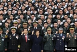 FILE - South Korean President Park Geun-Hye cheers with new military officers during a military commissioning ceremony at Gyeryongdae, South Korea's main military compound, March 4, 2016