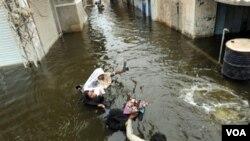 Seorang pria Pakistan melewati genangan air akibat banjir yang sudah mulai menyusut.