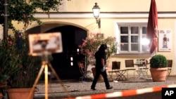 Un agent de police examine la scène après une explosion, dimanche 24 juillet 2016, à Ansbach, Allemagne, le lundi 25 Juillet, 2016.