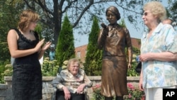 Madeline Piller (L), who started the interest in the 'Radium Girls' five years ago - and whose father created the statue - and two original workers from the factory, Pauline 'Toots' Fuller (C) and June Menne (R), after the statue is unveiled, September 2,