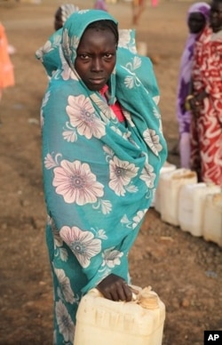 A woman leaving water point with empty jerry can - fights are common as desperation sets in