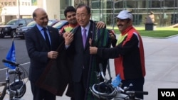 Afghan Ambassador to the UN Mahmoud Saikal, left, watches as Firoz Khan, second from left, and Nader Shah Nangarhari, right, give U.N. Secretary-General Ban Ki-moon a traditional Afghan chapan. (M. Besheer/VOA)