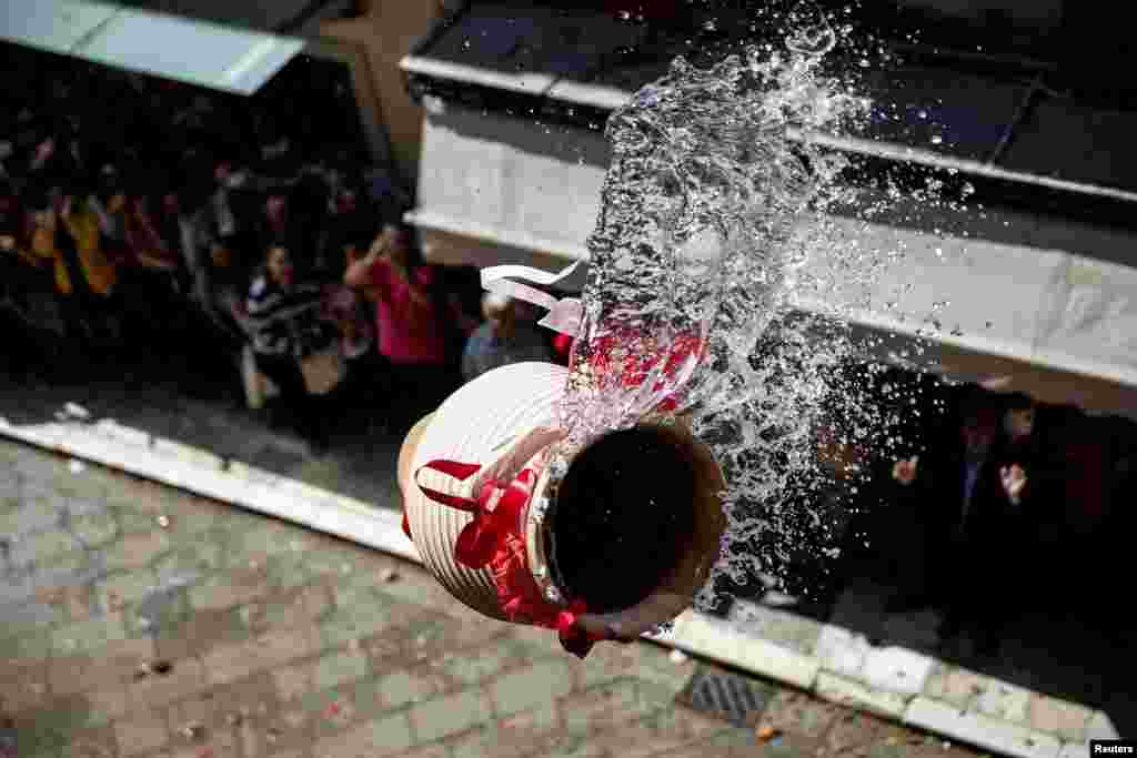 "A clay pot full of water is thrown from a balcony during the Greek Orthodox Easter tradition of ""Botides"" on Holy Saturday marking the so-called ""First Resurrection"", on the island of Corfu, Greece, April 30, 2016."