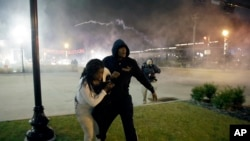 Protesters run for shelter as smoke fills the streets after the announcement of the grand jury decision not to indict police officer Darren Wilson in the fatal shooting of Michael Brown, an unarmed black 18-year-old, Nov. 24, 2014, in Ferguson, Missouri.