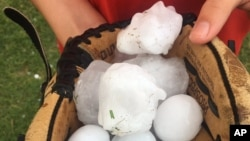 This photo provided by Stacey Valdez shows hail Valdez took in Sayre, Okla., May 16, 2017. The U.S. Midwest was hit by a large storm system again on Wednesday.