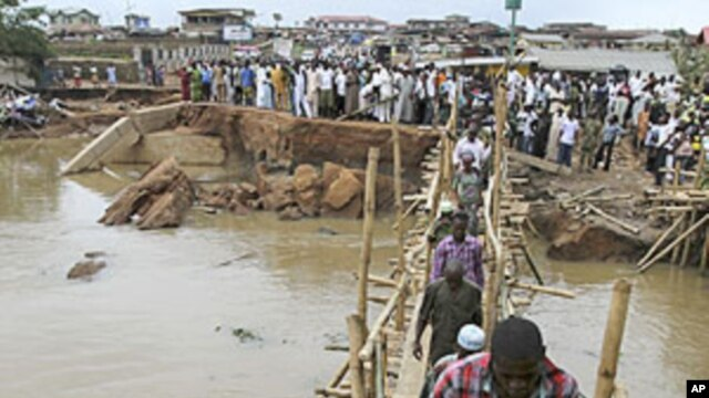 People queue to pass through a make-shift bridge after an heavy flood swept away a connecting bridge in Nigeria's south-west city of Ibadan,  August 30, 2011.