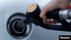A driver fills up with fuel at a Shell petrol station in London, Britain, May 15, 2013.